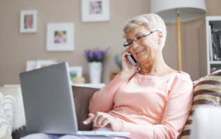 Senior woman on laptop with phone